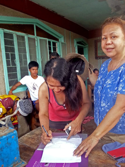 Meine Patentante Marilou (rechts) übergibt die Baumaterialien, die von den Spendengeldern gekauft wurden, an die Bewohner von Danao (c) Marilou Misagal-Bosshammer