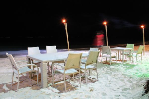 """Restaurant """"Caruso"""": Tisch und Stühle am Strand."""