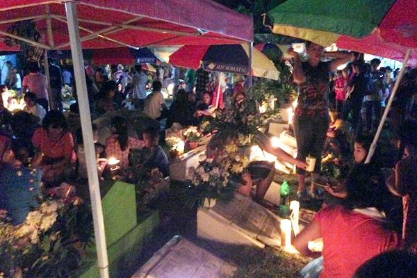 Filipinos sitzen zwischen Gräbern an Allerheiligen.