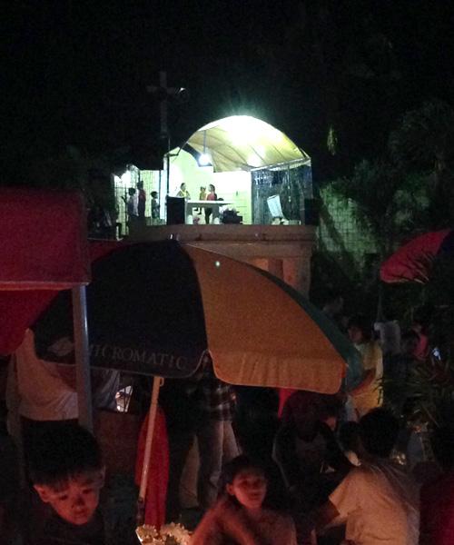 Auf einer Art Bühne spricht der Priester zu den Filipinos auf dem Friedhof.