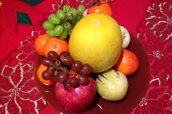 Ein Obstteller mit Trauben, Mandarinen, Granatapfel und Honigmelone