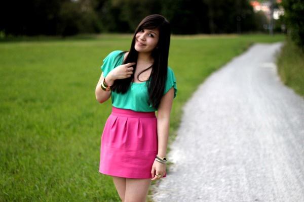 Junge Frau im grünen Shirt und pinkem Rock.