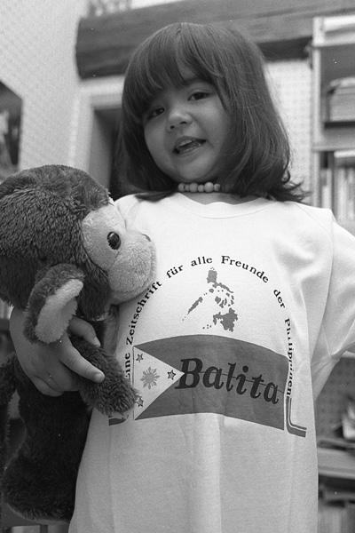 """Mädchen mit Plüsch-Affe im Arm und T-Shirt mit Aufdruck """"Balita""""."""