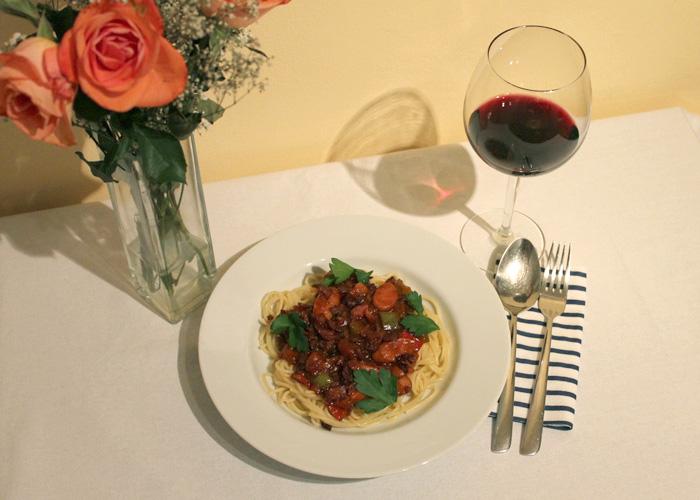 Spaghetti Philippinische Spaghetti auf einem Teller mit Rotwein und Rosen.philippinische Art.