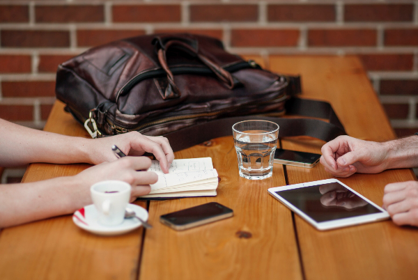 Tisch mit zwei arbeitenden Personen, Notizbuch, Tablet, Tasche und Smartphone